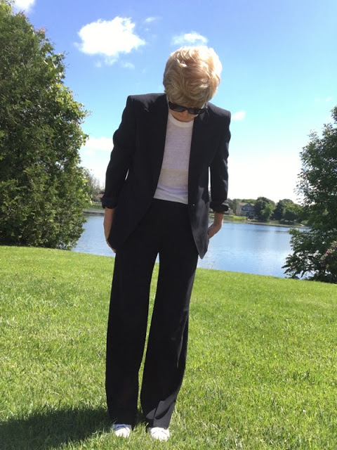 woman in navy suit, white tee, and white sneakers, on a lawn in front of a river