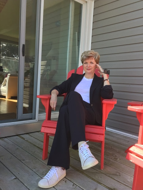 woman in a navy pantsuit, white tee, and white sneakers sitting in a red Adirondack chair
