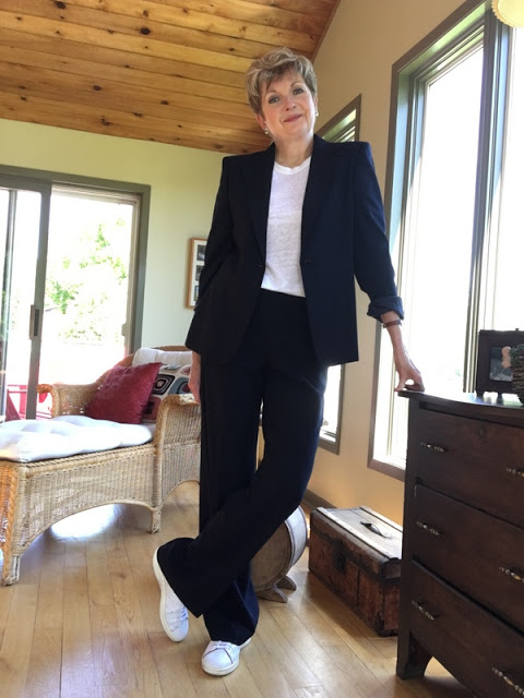 woman in a navy pantsuit, white tee, and white sneakers leaning against a chest of drawers
