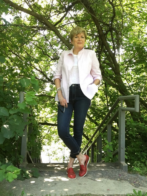 woman in pink shirt, white tee, red loafers, and jeans at top of stairway down to the Rideau River
