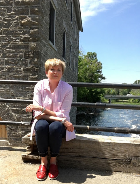 woman in pink shirt, jeans and red loafers sitting on the dam at Watson's Mill, Manotick