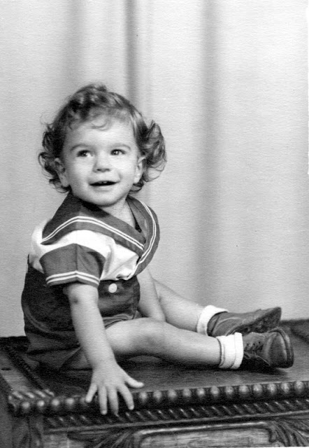 small boy posing in a sailor suit