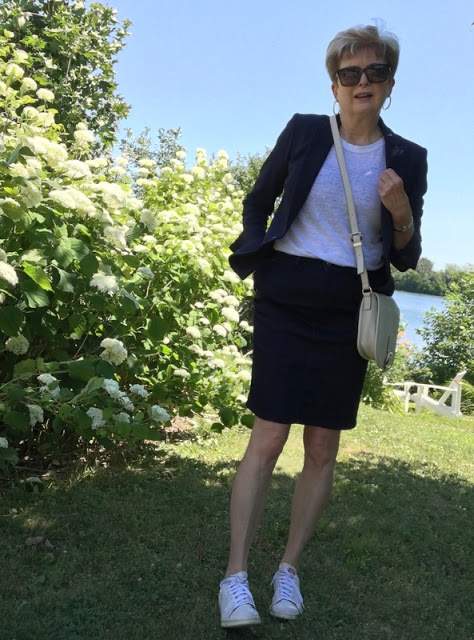 woman in navy skirt and jacket, white tee, and white sneakers. Posing in front of white hydrangeas.