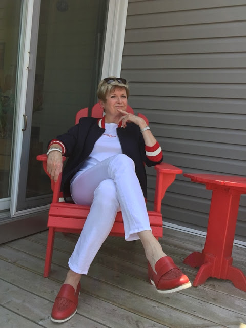 woman in white jeans, red loafers, and a navy, red and white baseball jacket, sitting in a red Adirondack chair