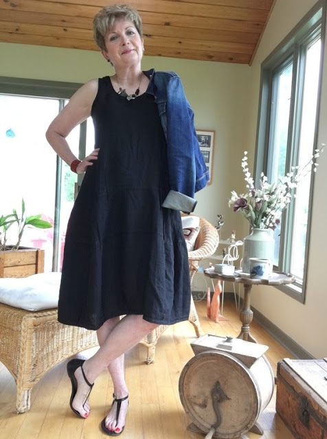 woman in black dress and sandals holding a jean jacket