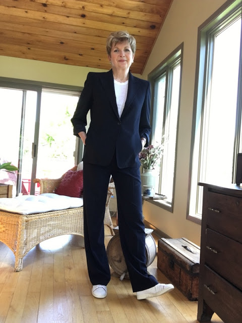 woman in navy pants suit, white sneakers, and white tee