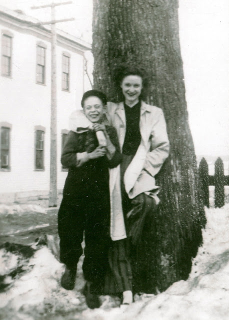 vintage photo of woman leaning against a tree with her arm around he neck of a boy