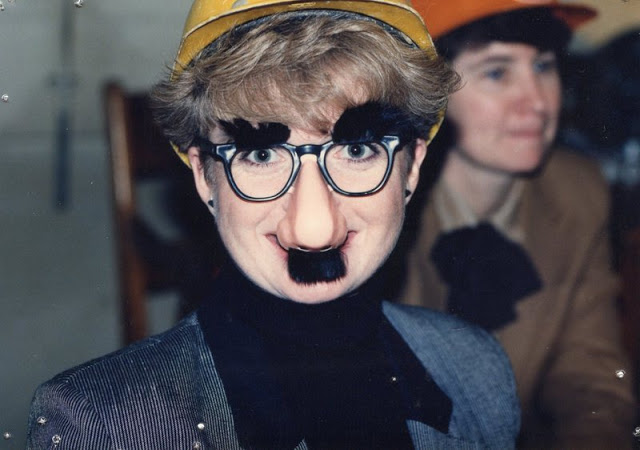 woman in black turtleneck and suit jacket wearing a hard hat and a Groucho Marx disguise.