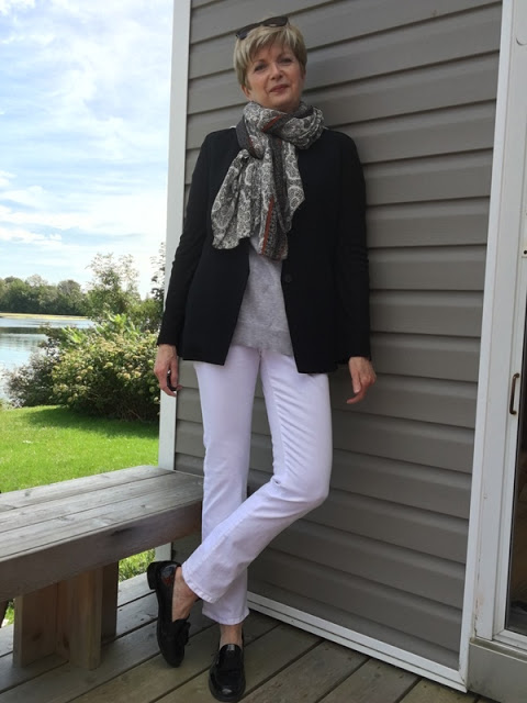 woman in black jacket, white jeans, and scarf posing on a deck with river in background