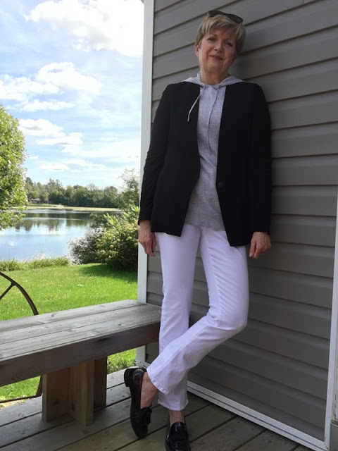 woman in black jacket and white jeans posing on a deck with river in background