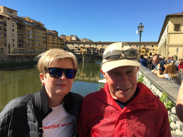 Man and woman smiling in Florence with the Ponte Vecchio in the background