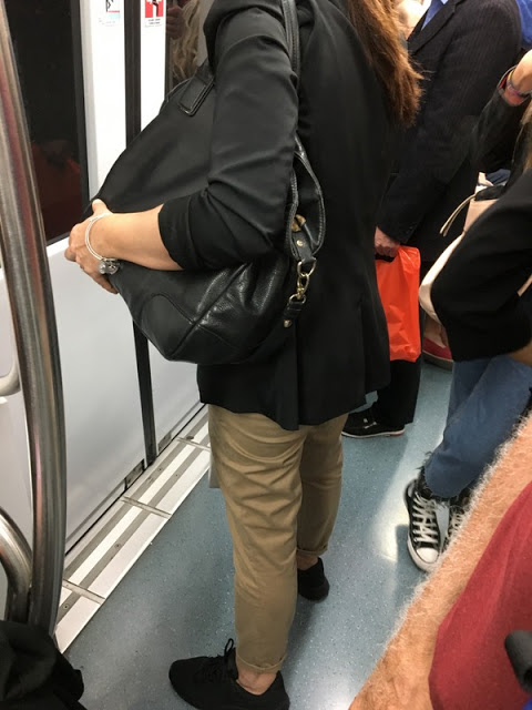 woman in blazer, pants, and sneakers on the subway in Rome