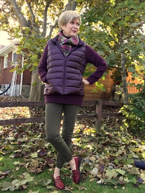 woman in burgundy sweater and vest, scarf, and khaki jeans, standing under a tree amidst fallen leaves.