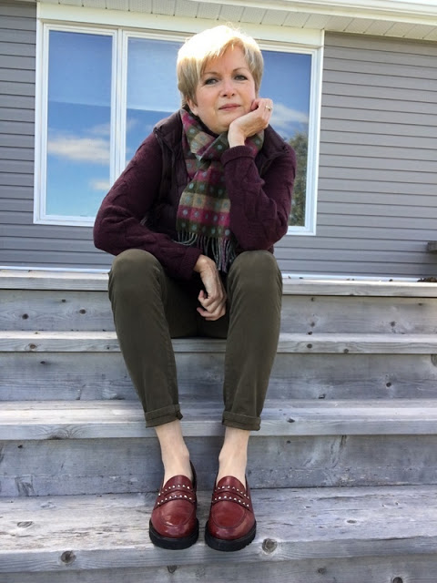 woman wearing burgundy sweater and down vest, scarf, khaki jeans and burgundy shoes sitting on the steps of a deck