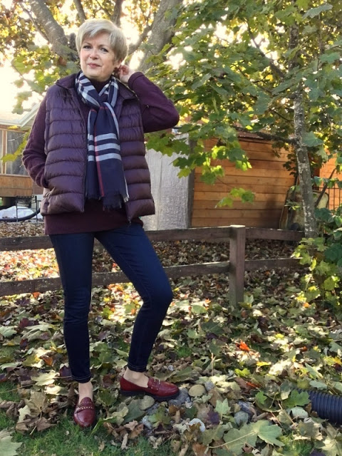 woman in burgundy sweater and vest, scarf and blue jeans, standing under a tree amidst fallen leaves.