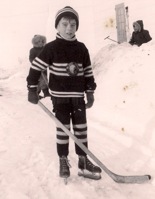 young boy in vintage hockey sweater, and socks with his stick