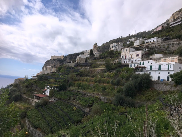 white houses of a village in Italy cling to the cliffs along the Amalfi Coast