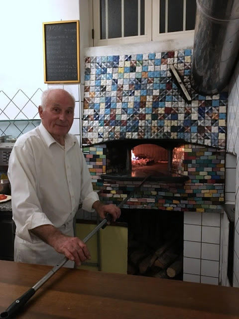 white haired owner of a pizzeria in Agerola, Italy removes pizza from the oven