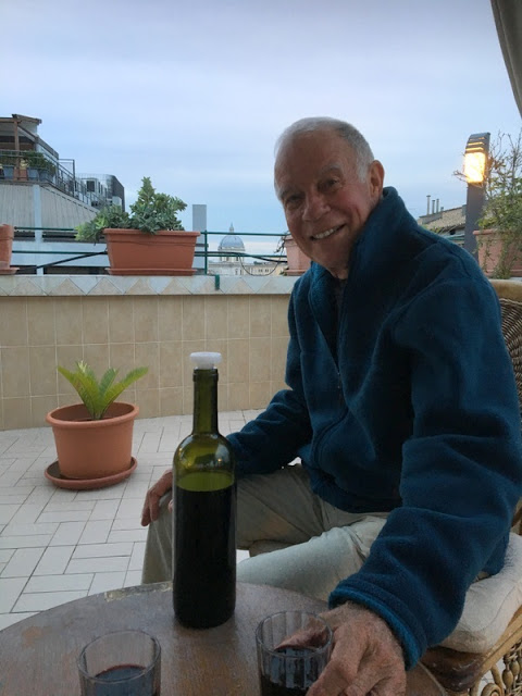 smiling man drinking wine on a rooftop terrace