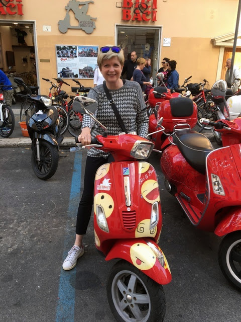 smiling woman on a red Vespa in Rome, Italy