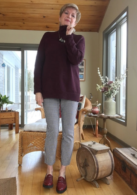 woman in checked pants, and burgundy sweater and loafers.