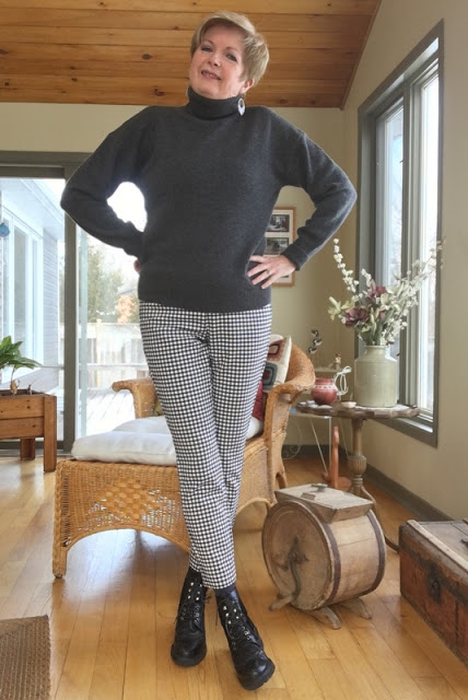 woman in charcoal turtleneck sweater, checked pants, and black ankle boots