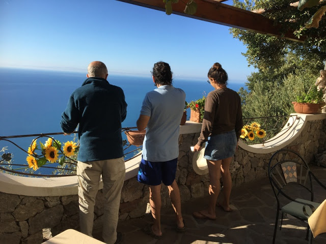 three people look out to sea from a terrace