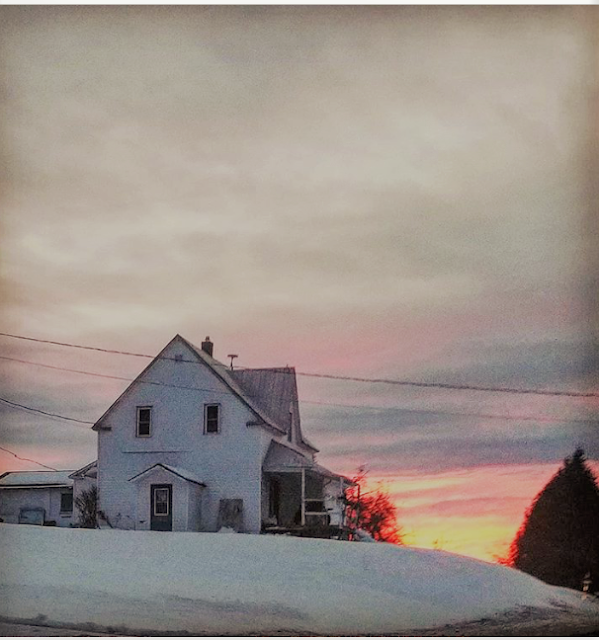 Winter scene in Kingsclear, New Brunswick. White farmhouse, surrounded by snow, with sunset behind