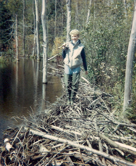 woman carrying a fishing rod, walking on top of a beaver dam, somewhere in the Ottawa Valley in the 1980's