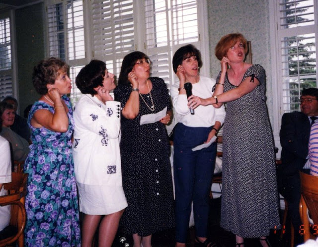 Five women singing and pulling their earlobe