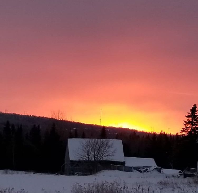 winter sun setting behind a forested hill, snow covered fields and old barns in the foreground