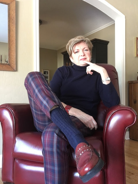 woman in plaid pants, navy sweater and socks, and burgundy loafers sitting in a burgundy chair