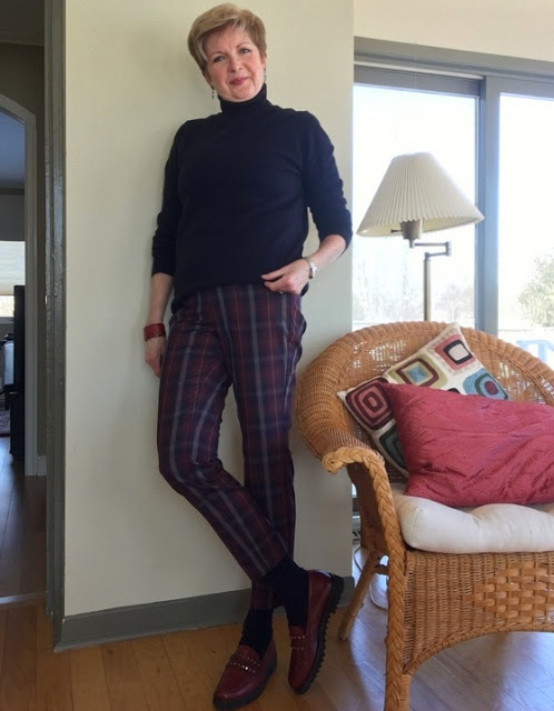 woman in plaid pants, navy sweater and socks, and burgundy loafers leaning against a wall