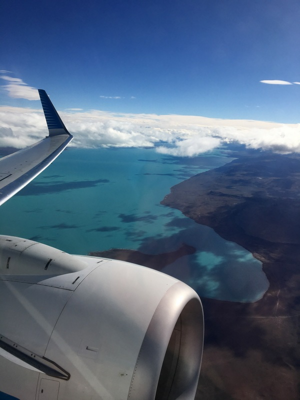 The view from our plane as we flew from El Calafate to Bariloche in Argentina. Blue sky, blue water, and the plane's wing and engine.