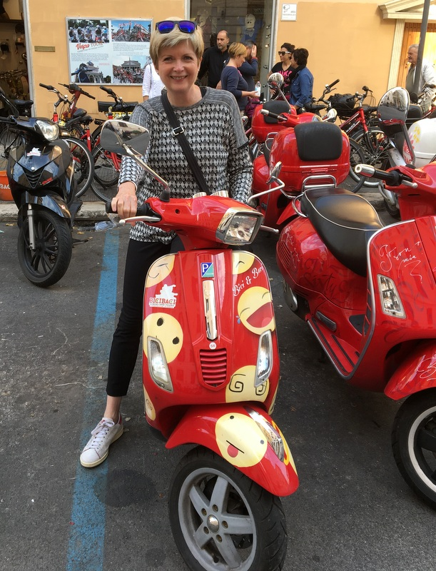 On a red Vespa in Rome in October 2018. Wearing my black and white tee, black pants, and white Stan Smith sneakers.